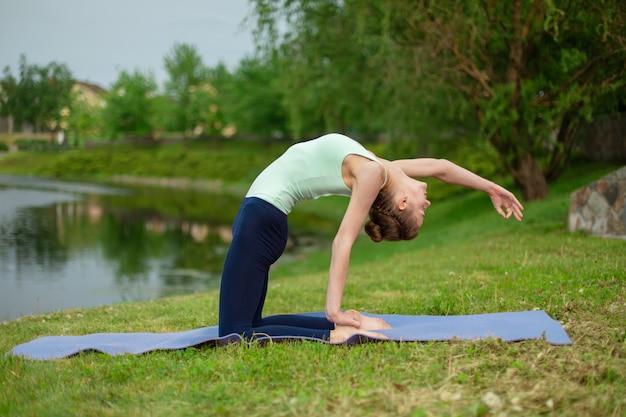 Une jeune yogi brune mince effectue des exercices de yoga complexes sur de l'herbe verte