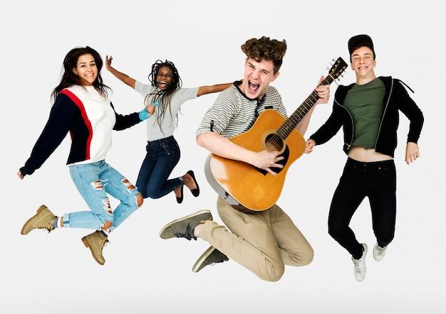 Jeunes adultes sautant avec portrait de studio de guitare