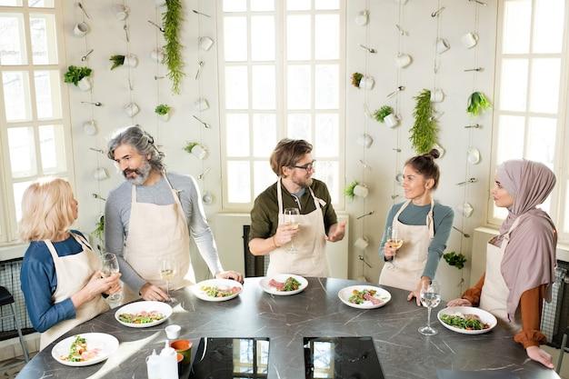 Jeunes et adultes en tabliers debout près d'une table ronde dans un studio de cuisine, se parlant et buvant du vin avant de goûter à la nourriture