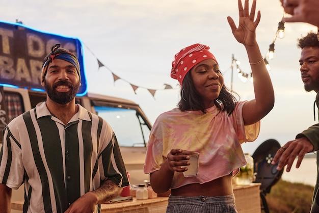 Jeunes africains buvant des boissons alcoolisées et dansant ensemble lors d'une fête sur la plage en plein air
