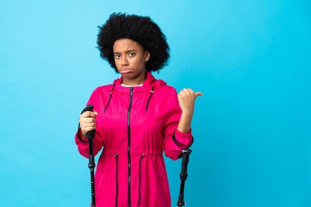 Les jeunes afro-américains avec sac à dos et bâtons de randonnée sur le mur bleu malheureux et pointant vers le côté