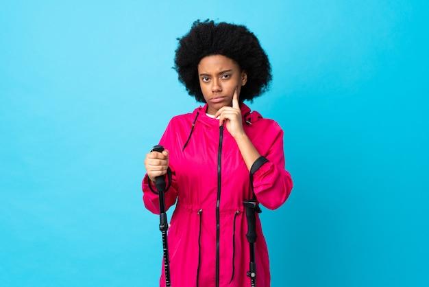 Les jeunes afro-américains avec sac à dos et bâtons de randonnée sur le mur bleu et la pensée