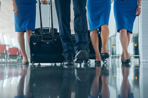 Jeunes agents de bord caucasiens en chaussures à la mode marchant le long du terminal de l'aéroport