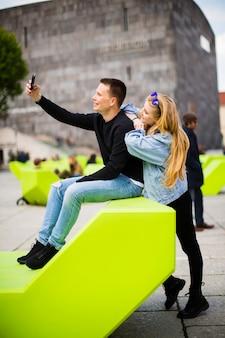 Les jeunes à l'aide de téléphone mobile sur le banc moderne sur rue à vienne, autriche