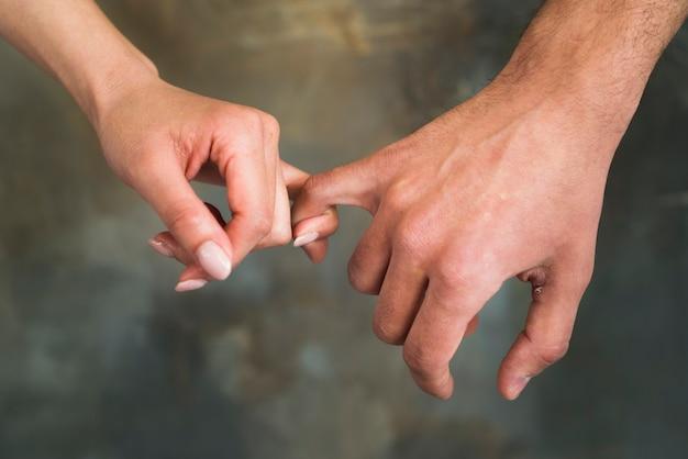 Jeunes amants méconnaissables tenant des petits doigts