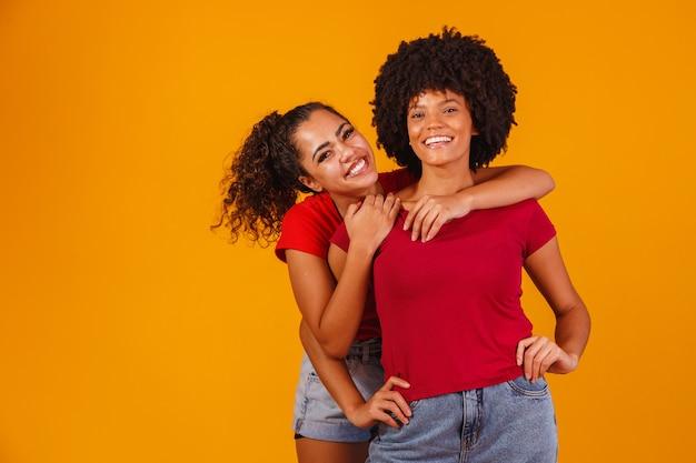 Jeunes amies afro belles et heureuses souriant à la caméra.