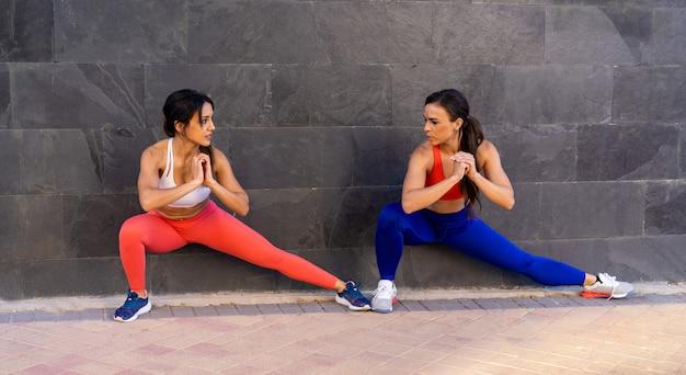 Jeunes amies caucasiennes faisant des exercices et s'étirant à l'extérieur