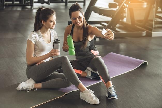 De jeunes amies font de l'exercice dans la salle de sport en prenant des photos