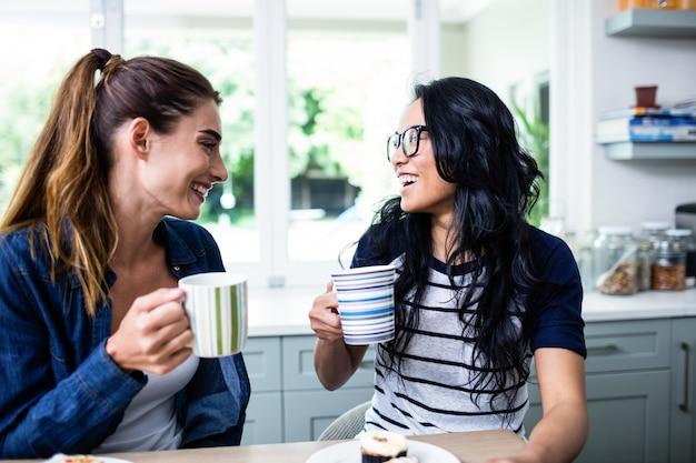 Jeunes amies rire en buvant du café
