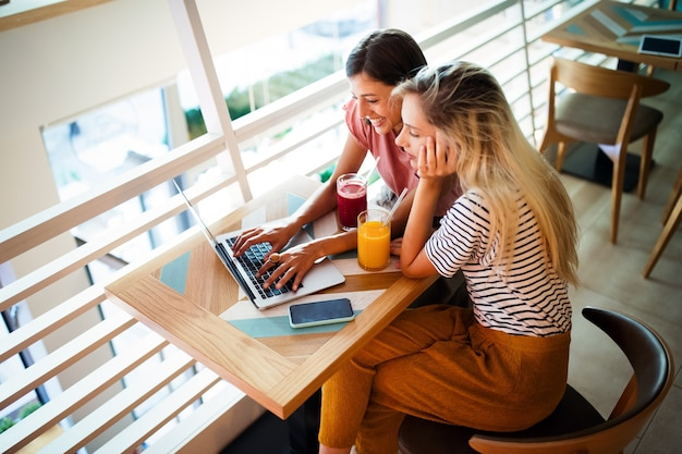 Jeunes amies surfant sur internet et s'amusant ensemble