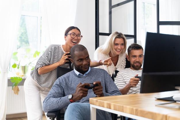 Jeunes amis adultes s'amusant en jouant à des jeux vidéo