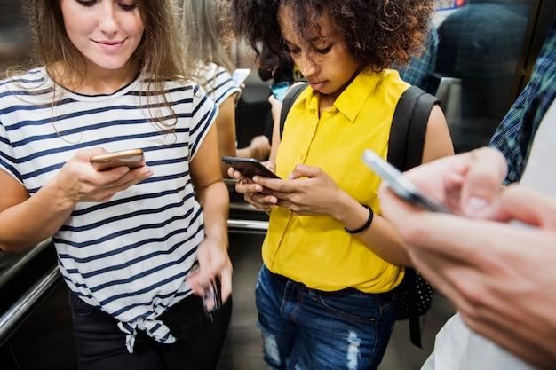 Jeunes amis adultes utilisant des smartphones dans le métro