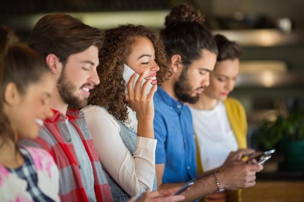 Jeunes amis à l'aide de téléphones mobiles