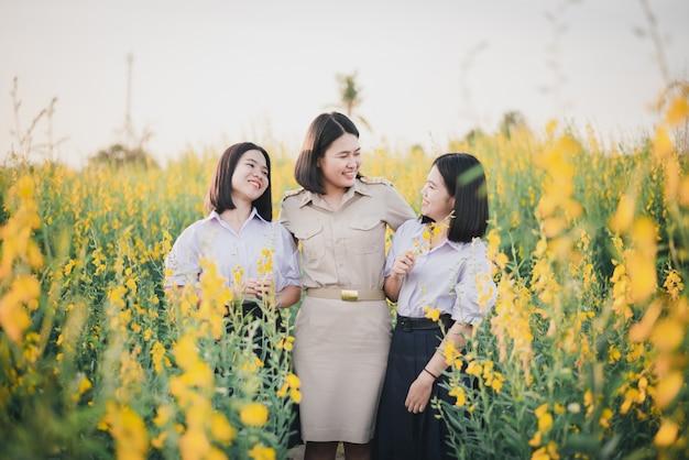 Jeunes amis asiatiques dans un champ de fleurs de crotalaria