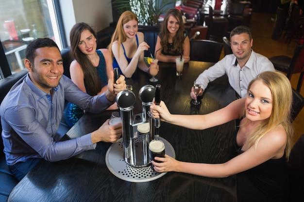 Jeunes amis assis ensemble et tirant des pintes dans un restaurant
