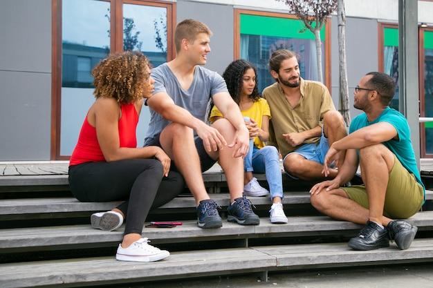 Jeunes amis assis sur les marches