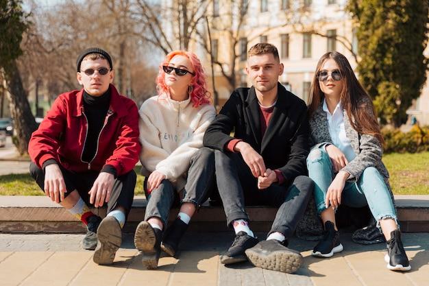 Jeunes amis assis sur un trottoir en ville