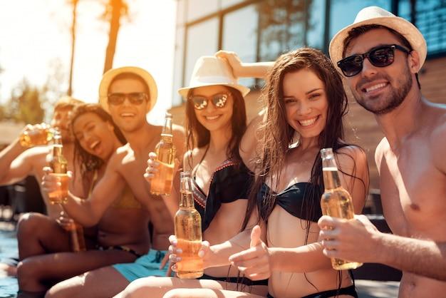 Jeunes amis avec des boissons alcoolisées au bord de la piscine