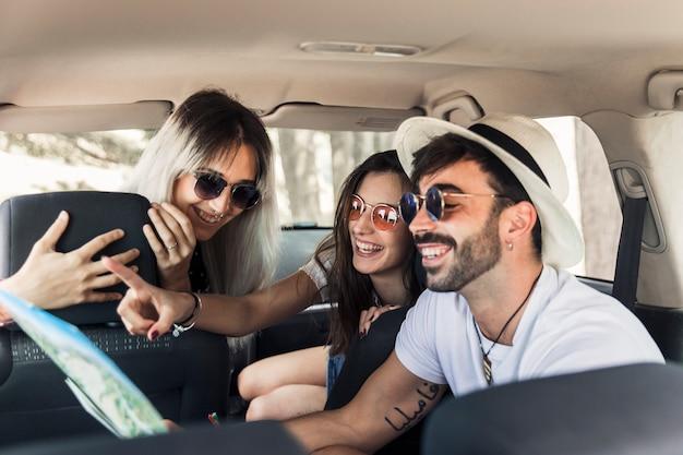 Jeunes amis branchés assis à l'intérieur de la voiture moderne en regardant la carte