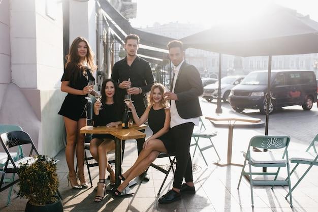 Jeunes amis buvant du champagne sur une terrasse