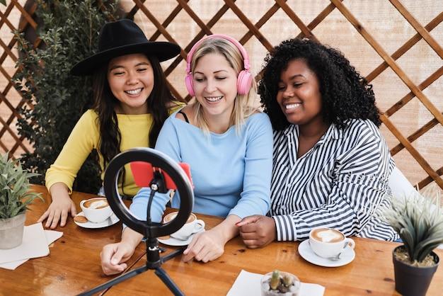 Jeunes amis divers en streaming en ligne avec un appareil photo pour téléphone portable à l'extérieur du restaurant - focus sur le visage de la femme au centre