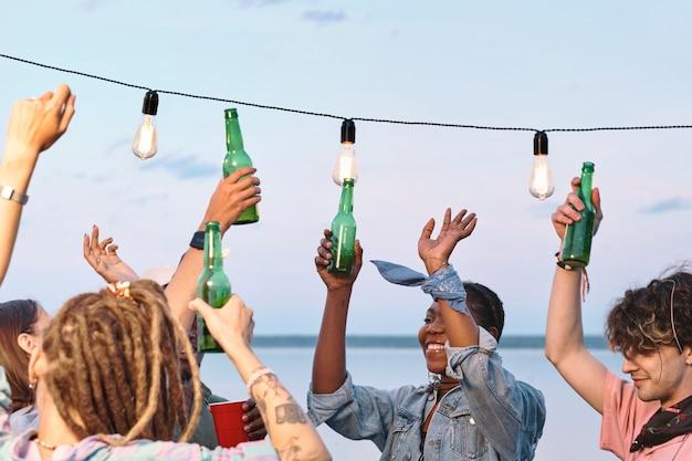 Jeunes amis extatiques avec des bouteilles de bière dansant au bord de l'eau