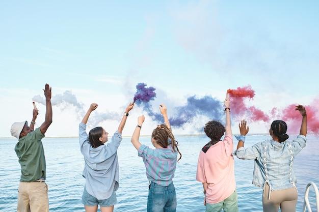 Jeunes amis extatiques avec des pétards multicolores dansant devant le bord de l'eau