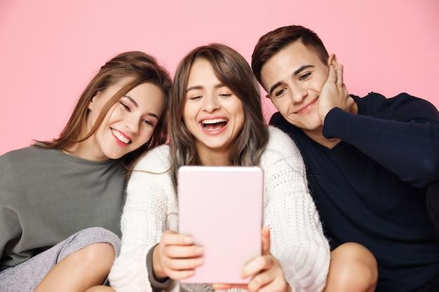 Jeunes amis faisant selfie sur tablette rose