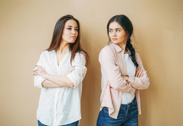 Jeunes amis filles bouleversées dans offensé occasionnel les uns aux autres isolé sur le fond beige