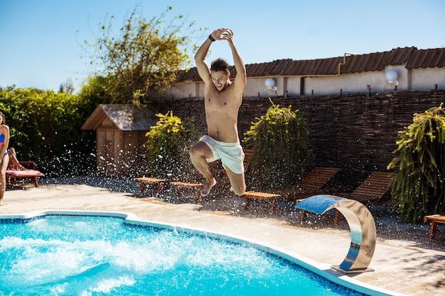 Jeunes amis gais souriant, relaxant, sautant dans la piscine