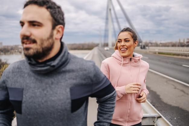 Jeunes amis hétérosexuels souriants positifs en tenue de sport en cours d'exécution sur le pont par temps nuageux.