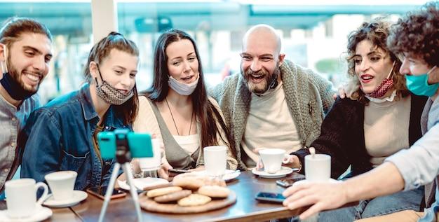 Jeunes amis heureux partageant du contenu sur une plate-forme de streaming portant un masque facial
