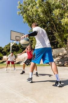 Jeunes amis jouant au basketball sur le court en plein air