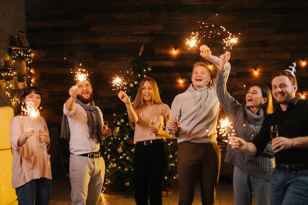 De jeunes amis joyeux dansent avec des lumières bengali, s'amusent et fêtent le nouvel an sans soucis. les gens dansent avec des cierges magiques dans une pièce sombre et tintent avec des verres de champagne.