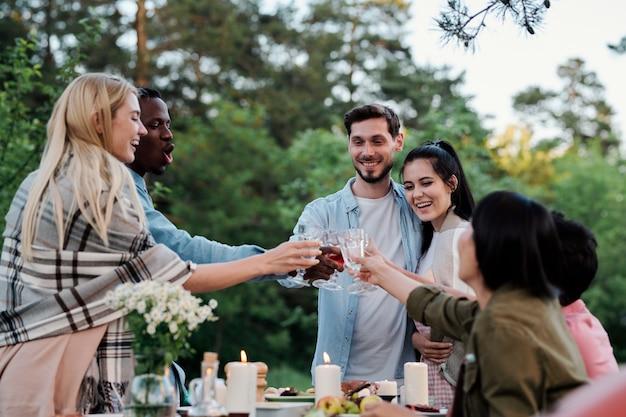 Jeunes amis joyeux de diverses ethnies se réjouissant avec des verres de vin sur une table servie avec des plats faits maison et des bougies allumées