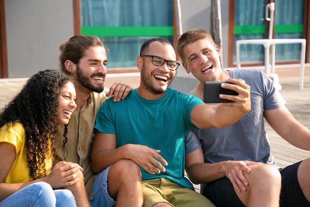 Jeunes amis joyeux pendant le chat vidéo
