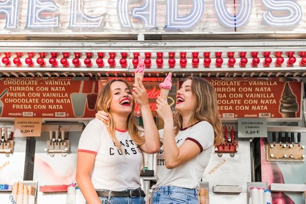 Jeunes amis, manger des glaces dans le parc d'attractions