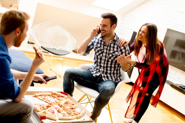 Jeunes amis, manger de la pizza à la maison et s'amuser