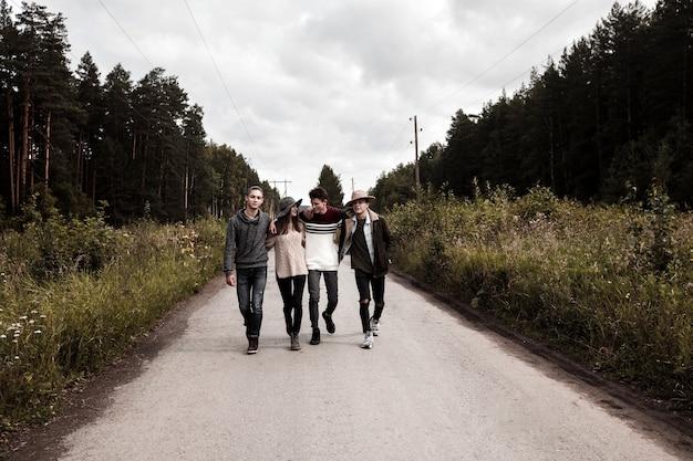 Jeunes amis marchant sur la route de campagne