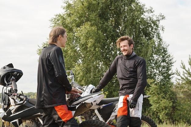 Jeunes amis masculins positifs debout à motos en forêt et parler de motocyclisme