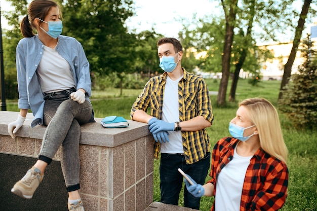 Jeunes amis masqués et gants de loisirs dans le parc, quarantaine. personne de sexe féminin marchant pendant l'épidémie, soins de santé et protection, mode de vie pandémique