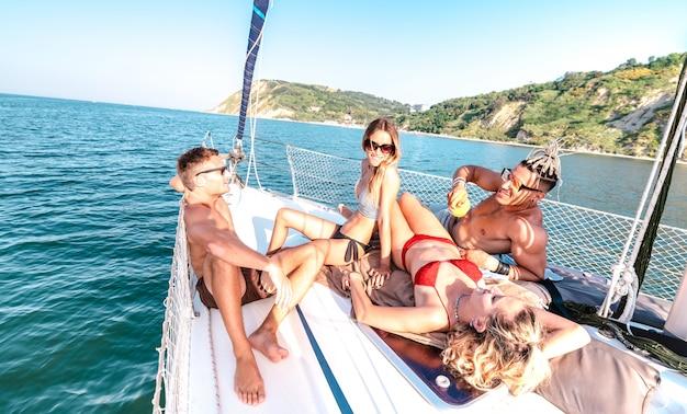 Jeunes amis millénaires se détendre sur un voilier en mer