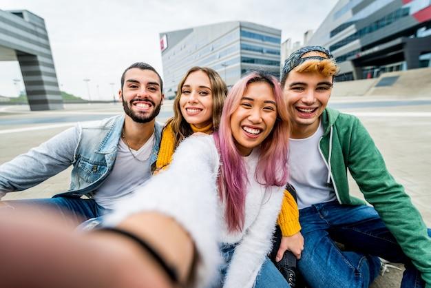 Jeunes amis multiraciaux prenant un portrait de selfie à l'extérieur