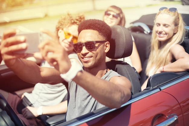 De jeunes amis prennent un selfie dans une voiture cabriolet