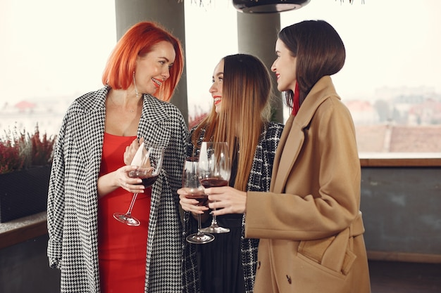 Les jeunes amis qui rient de boire du vin rosé à l'extérieur