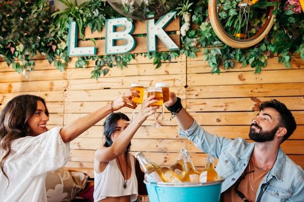 Jeunes amis ratissant avec de la bière