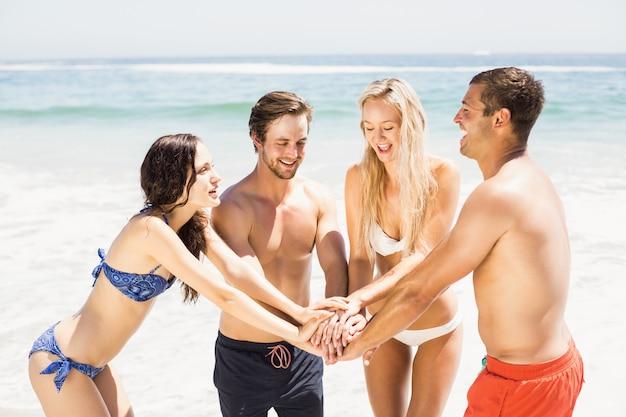 Jeunes amis réunissant leurs mains sur la plage