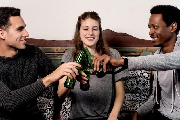 Jeunes amis s'amusant avec des bières à la maison
