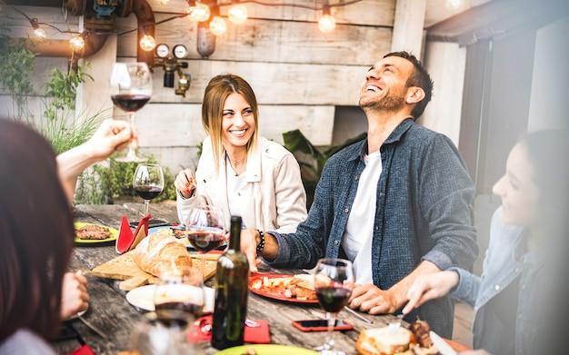Jeunes amis s'amusant à boire du vin rouge sur le balcon au dîner de la maison