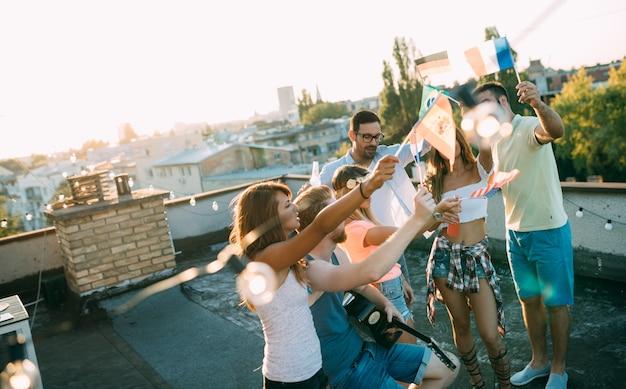 Jeunes amis s'amusant lors d'une fête sur le toit, jouant de la guitare, chantant, dansant et se relaxant